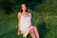 Gravid flickasammanträde på gräset Royaltyfri Bild