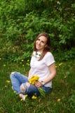 Gravid flickasammanträde på gräsmatta arkivfoton
