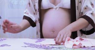 Gravid flickastrykningkläder arkivfilmer