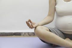 Gravid görande yoga i lotusblommaposition Arkivfoto
