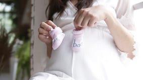 Gravid härligt kvinnasammanträde på fönsterbrädan vid fönstret Rymma behandla som ett barn byten för ` som s gör små moment på he stock video