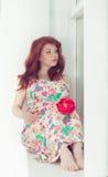 Gravid härligt rödhårigt kvinnasammanträde på en fönsterfönsterbräda på fönstret arkivfoton
