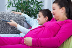 Gravid hållande ögonen på television för mamma och för son tillsammans Royaltyfria Foton