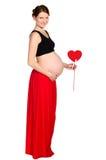 Gravid i röd kjol med pappers- hjärta i händer arkivbilder