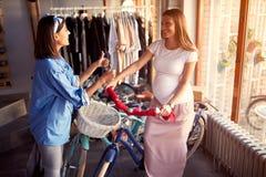 Gravid kvinna f?r s?ljarekvinnaportion till att k?pa den nya cykeln i lager arkivfoton