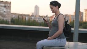 gravid kvinna f?r celltelefon arkivfilmer