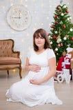 Gravid kvinna hemma med det dekorerade julträdet, tappning så Arkivfoto