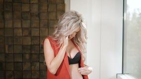 Gravid kvinna i den röda skjortan, jeans och den svarta behån som blir nära fönstret med smartphonen Härlig framtida moder stock video