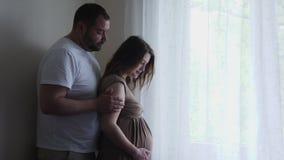 Gravid kvinna i en brun kl?nning och hennes make i en vit t-skjorta arkivfilmer