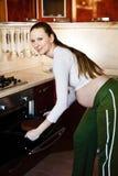 Gravid kvinna i en kökmatlagning royaltyfri fotografi