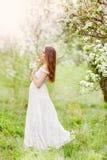 Gravid kvinna i en klänning i ett fält av blommor arkivbild