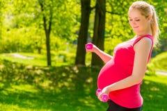 Gravid kvinna i en rosa skjorta som gör övningar Arkivbilder