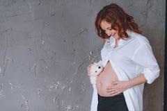 Gravid kvinna i en skjorta för vit man` s, en studiostående Se midsectionen Med en nallebjörn framme av honom Royaltyfria Bilder