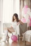 Gravid kvinna i en vit nattlinne med ballonger Arkivbild