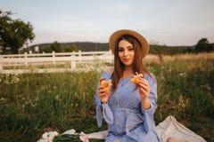 Gravid kvinna i fältet som äter den nya drog tillbaka frasiga gifflet sund mat Den unga kvinnan äter mycket aptitretande fotografering för bildbyråer