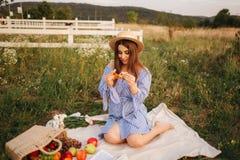 Gravid kvinna i fältet som äter den nya drog tillbaka frasiga gifflet sund mat Den unga kvinnan äter mycket aptitretande royaltyfri foto