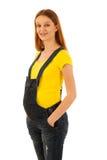 Gravid kvinna i gul t-skjorta och jeans som isoleras över vit b Arkivfoton