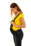 Gravid kvinna i gul t-skjorta och jeans som isoleras över vit b Royaltyfri Foto