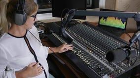 Gravid kvinna i hörlurar på jobbet, modern mamma på skadligt arbete arkivfilmer