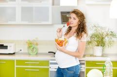 Gravid kvinna i kök Arkivbild
