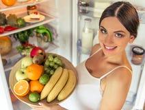 Gravid kvinna i köket royaltyfria foton