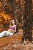 Gravid kvinna i natur i höst Royaltyfria Bilder
