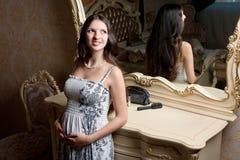 Gravid kvinna i near spegel för sovrum Royaltyfria Bilder