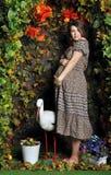 Gravid kvinna i trädgårds- seende studiostil Arkivbild