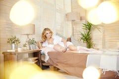 Gravid kvinna i underkläder på min säng Den blonda flickan förbereder sig att bli en moder Barnsbörd en lycka för kvinna` s Sexig Royaltyfri Foto