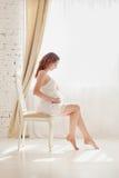 Gravid kvinna i vitkläder i sovruminre arkivfoton