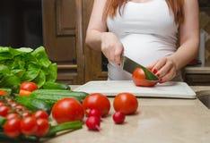 Gravid kvinna klippta nya grönsaker Arkivfoton