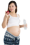 Gravid kvinna med äpplet och flaskan på den vita bakgrunden Arkivfoto