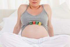 Gravid kvinna med behandla som ett barn kuber på henne buken 免版税图库摄影
