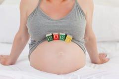 Gravid kvinna med behandla som ett barn kuber på henne buken 免版税库存图片