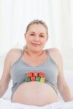 Gravid kvinna med behandla som ett barn kuber på henne buken 免版税库存照片