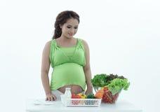 Gravid kvinna med bunken av sallad. Arkivbild