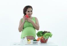 Gravid kvinna med bunken av sallad. Fotografering för Bildbyråer