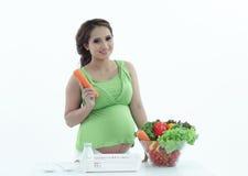 Gravid kvinna med bunken av sallad. Royaltyfri Bild