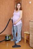 Gravid kvinna med dammsugaren Royaltyfri Fotografi