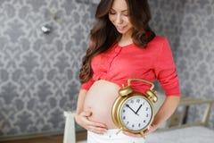Gravid kvinna med den stora klockan i hand Royaltyfria Foton