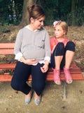 Gravid kvinna med dottern som vilar i parkera Royaltyfria Bilder