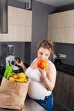 Gravid kvinna med en påse av nya frukt och grönsaker Arkivbild