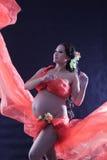 Gravid kvinna med en röd klänning. Arkivbild