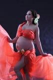 Gravid kvinna med en röd klänning. Fotografering för Bildbyråer