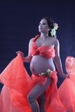 Gravid kvinna med en röd klänning. Arkivfoto