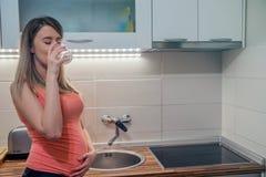 Gravid kvinna med exponeringsglas av vatten i handen, begrepp av sunt l Royaltyfri Bild