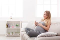 Gravid kvinna med exponeringsglas av vattensammanträde på soffan Royaltyfri Bild