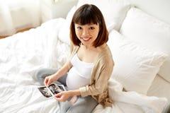 Gravid kvinna med foster- ultraljudbild hemma Royaltyfri Fotografi