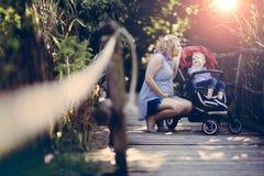 Gravid kvinna med hennes barn i pram Royaltyfri Fotografi