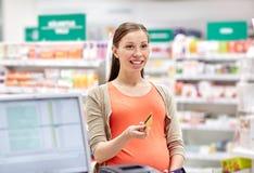 Gravid kvinna med kreditkorten i apotek royaltyfri fotografi